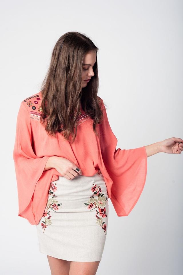 Blusa coral con detalle de bordado y mangas amplias