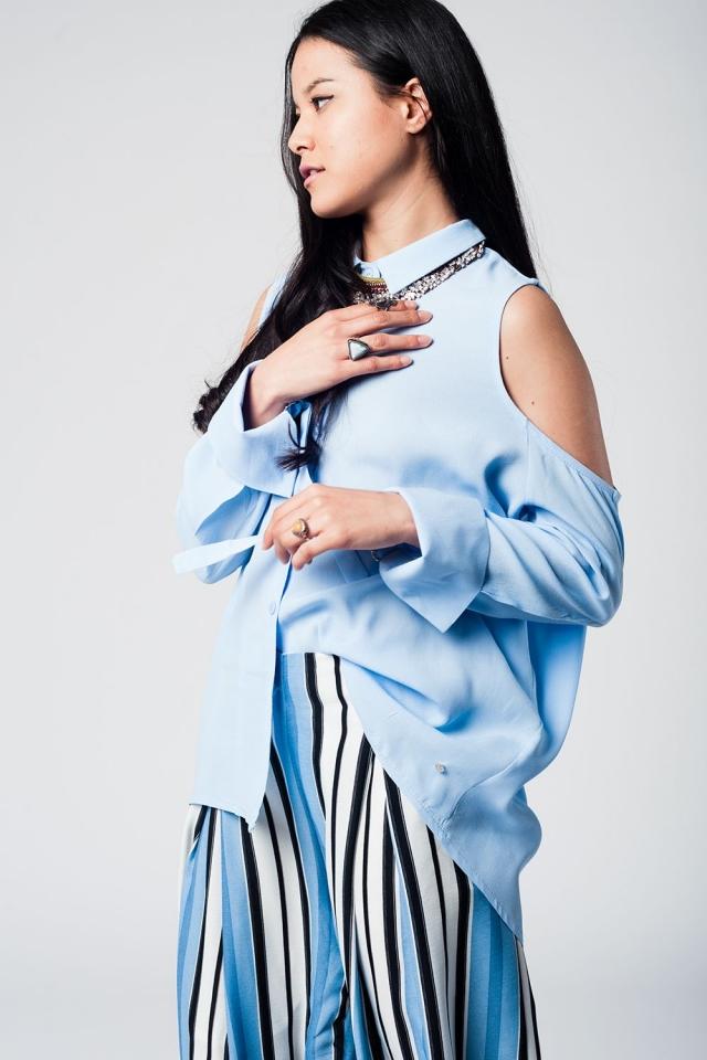 Camisa larga azul con hombros al aire y detalle de anilla en los puños