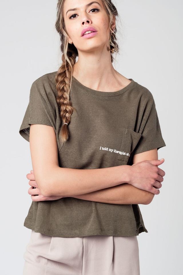 Camiseta color khaki con texto y bolsillo delantero