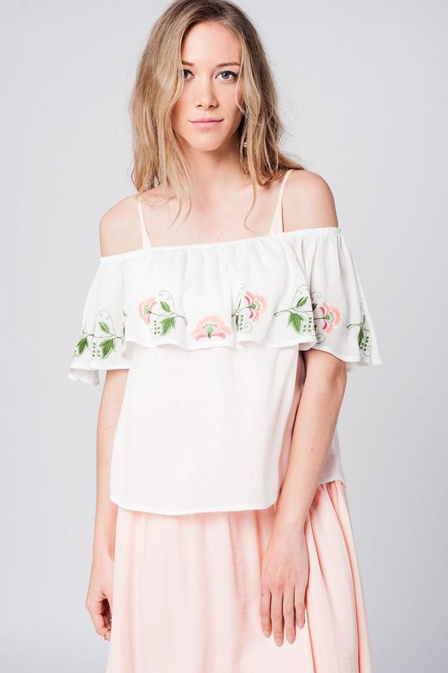 Blusa blanca con volante y detalle de flores bordadas