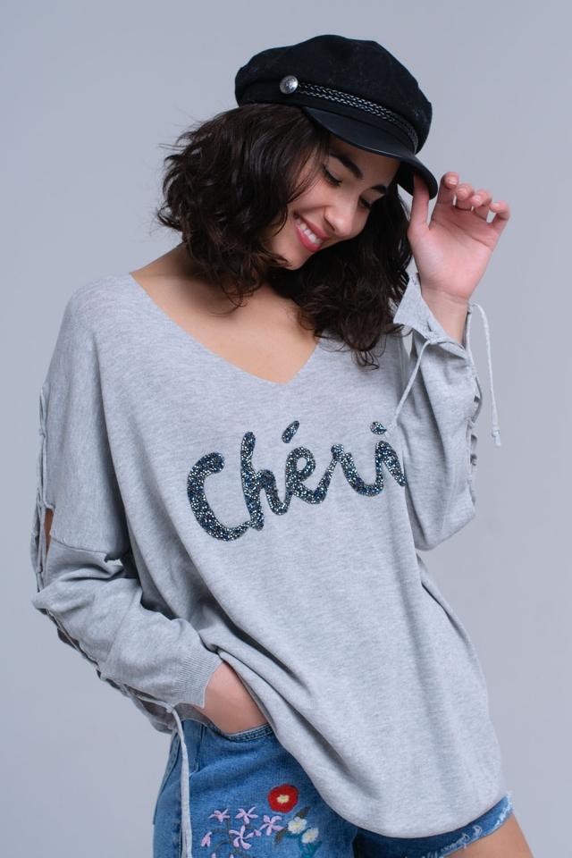 Suéter gris con slogan y cintas