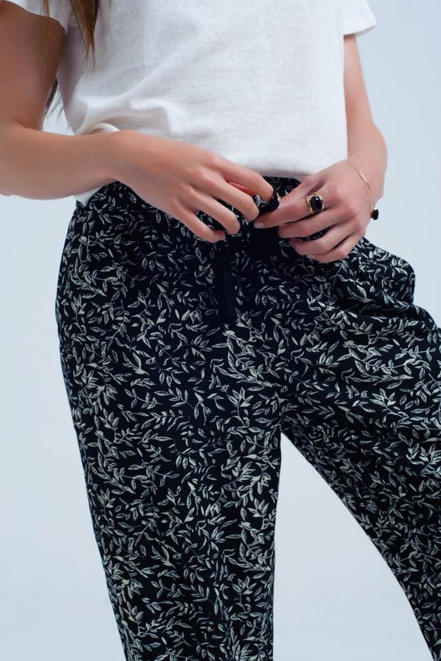 Pantalón negro con diseño de hojas blancas y bolsillos