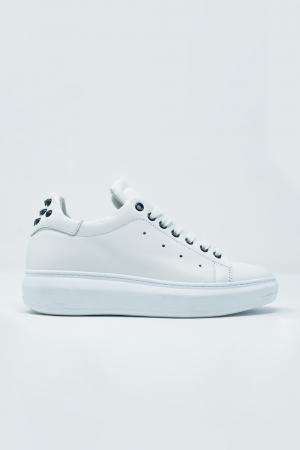 Zapatillas blancas planas con tachuelas negras