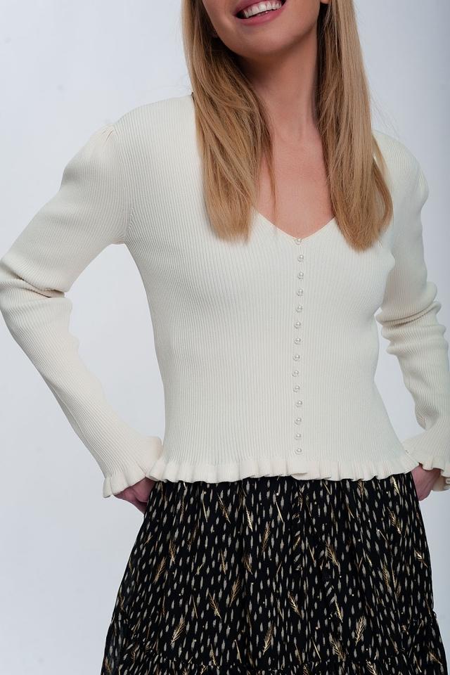 Jersey de canalé en color crema con detalle de botones de perlas