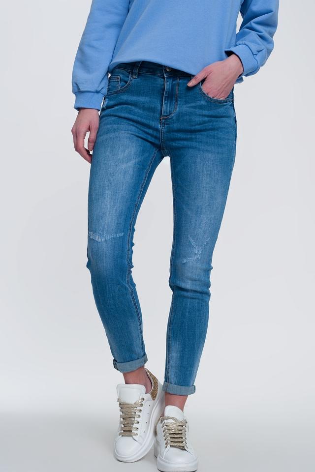 jeans ajustados de mezclilla clara con tobillos doblados y detalle rasgado