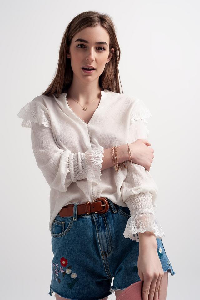 Blusa con volumen en las mangas y volantes en los puños en color crema
