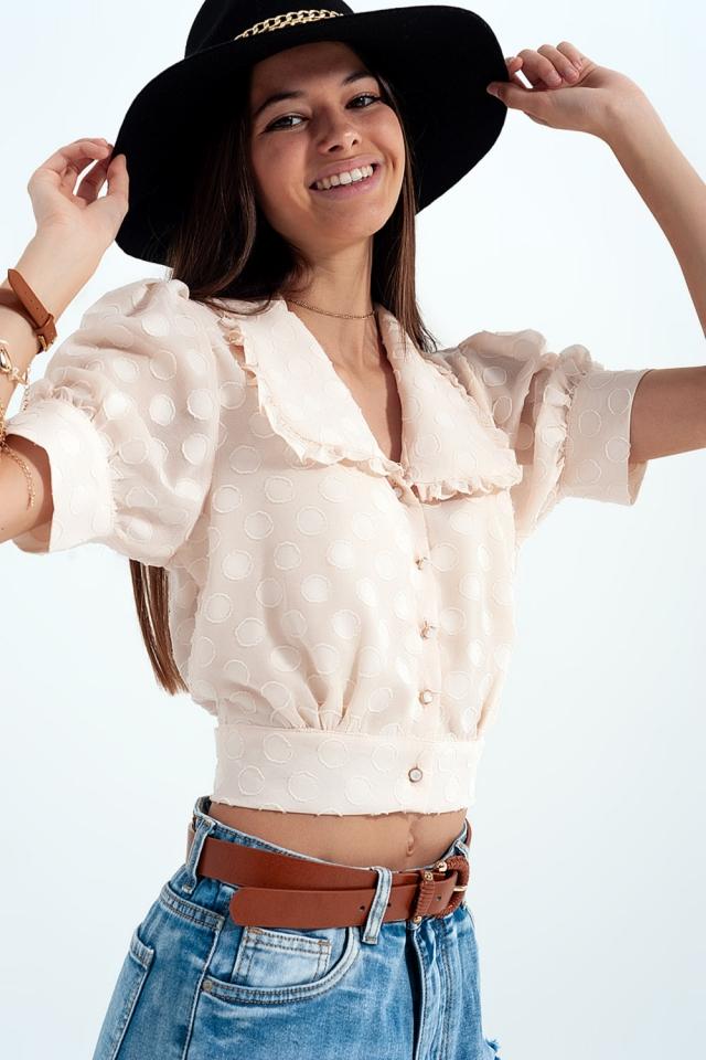 Blusa beige de lunares con cuello estilo babero y botones decorativos