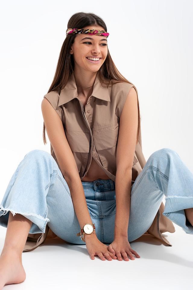 Camisa beige holgada sin mangas con hombreras y bolsillos utilitarios