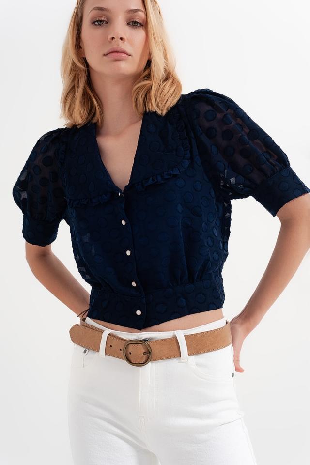 Blusa azul marino de lunares con cuello estilo babero y botones decorativos